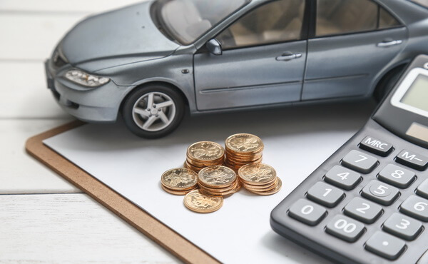 A small car, money and calculator at the table