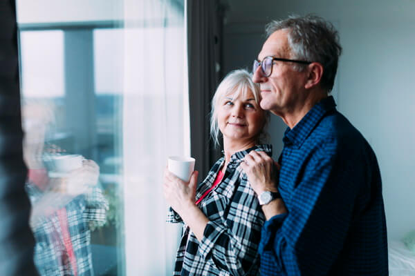 An older couple is standing by the window