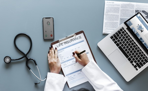 Doctor filling up a life insurance form